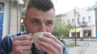Man drinking coffee at a sidewalk cafe table