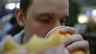 Man drinking tea and eating a hamburger at a fast food cafe