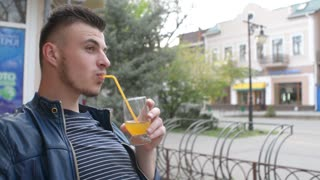 Man drinks orange juice from a glass - cafe on the terrace of old town