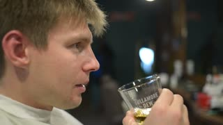 Man drinks Whiskey sitting in the Barbershop