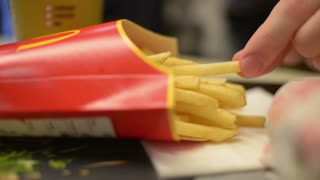 Man eats French fries at McDonald's cafe table