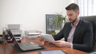 Man - Lawyer sitting in the Office and reading papers