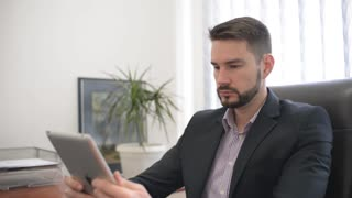 Man - Lawyer sitting in the Office using digital Tablet