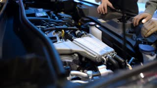 Man looks under the Hood of Toyota - inspecting engine at Auto Show