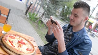 Man makes Photo of Pizza - outdoor cafe table in town