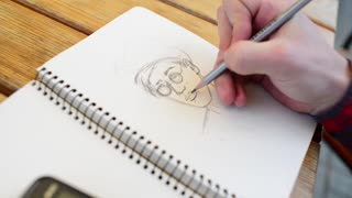 man paints an auto portrait with pencil in a notebook - close-up detail