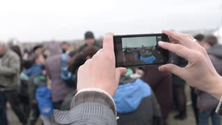 Man photographs and videos on the mobile phone crowd together
