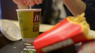 Man pours sugar into tea at a table fast-food cafe