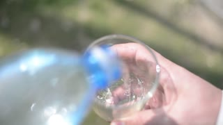 Man pours water from a plastic bottle into a glass - sammer in the city park