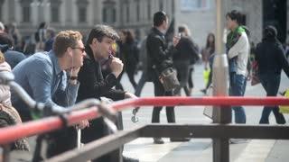 man smokes electronic cigarette near the Duomo in Milan