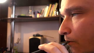 Man smoking Electronic Cigarette Pipe at Computer at Home - close-up day
