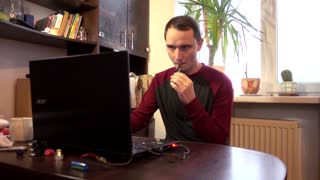 Man smoking Electronic Cigarette Pipe at Computer at Home - day