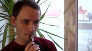 Man smoking Electronic Cigarette Pipe by the Window at Home - day