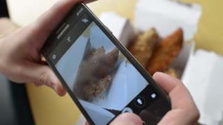 Man takes photo via Mobile Sell Phone of food Chicken and French fries Potato