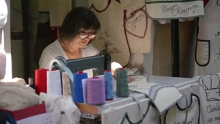 master embroiders aprons in old Italian town