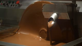 melted chocolate is poured into a vat - a workshop of chocolates