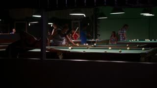 Men playing pool in the bar the night