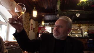Middle-aged Man with a Beard drink tastes the Wine at Restaurant cozy