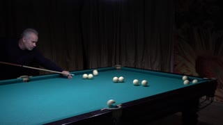 Middle-aged man with a beard playing billiards