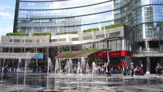 Milan business center city - pedestrians children on Piazza Gae Aulenti fountain