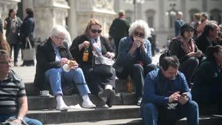 Milan center, people tourists eating sitting on granite steps
