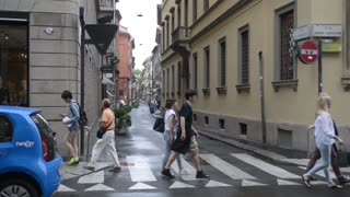 Milan city center Monte Napoleone. Vehicles and pedestrians walk and view windows.