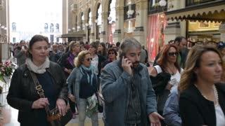 Milan, Galleria Vittorio Emanuele people walk looking in showcase shop - day
