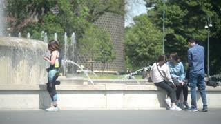 Milan, Italy - Fountain la turta di spus - Teenagers sitting having rest, spring