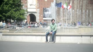 Milan, Italy - Fountain la turta di spus - young Man sitting alone
