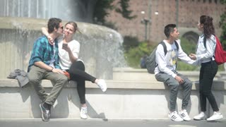 Milan, Italy - young lovers kissing with hugs near castle Sforzesco - spring day