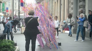 Milan, Italy,day street life - performance with brightly colored ribbons