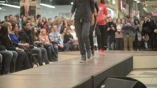 Models parade down catwalk podium - the audience watching a fashion show