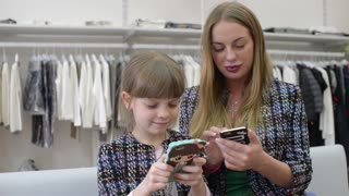 Mom and Daughter with Smartphones and Mobile phone shating in clothes store