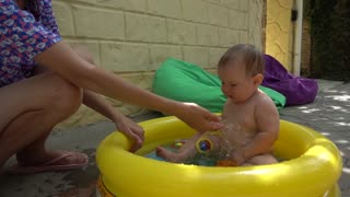 Mom bathes water small child in inflatable pool