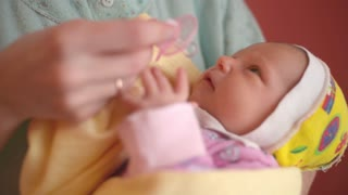 Mom gives the pacifier to a newborn baby - baby don't take the pacifier