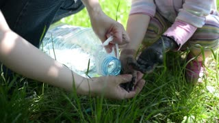 Mom washes with water dirty hands painted black of baby girl in park sunny day