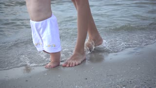 Mother And Baby Girl walk first Steps On The Sea Beach