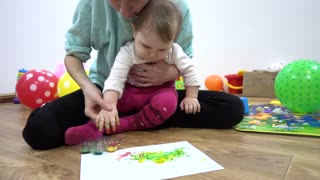 Mother and child baby girl playing with paints of different colors painting arms