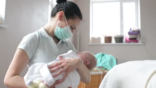 Mother in the respiratory mask holding sleepy newborn baby girl in hands