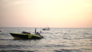 Motor boat near the sea shore swaying on the waves