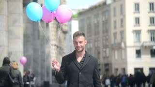nice guy smiling with colorful balls - the center of Milan Italy