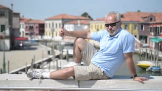 Old man posing and photographed against the backdrop picturesque canal in Venice