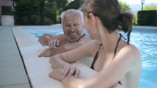 Old man talking to a young woman in the pool. summer filing