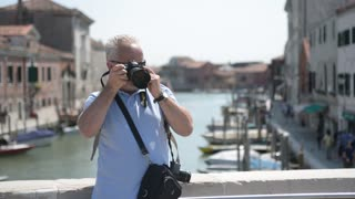 Old Man tourist photographer working outside Venice