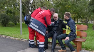 Paramedics rushing to help the old Man with a Heart Attack - Day in City Park