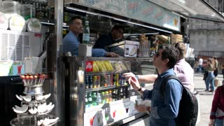 Passers buy food - street food stall in the center of Milan, Italy