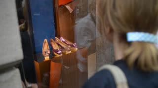 Passers look for shoes in the window on the street Monte Napoleone in Milan