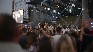 People clap and wave their hands at a rock concert