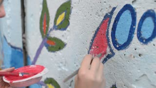 People painting the wall with brush and different colours