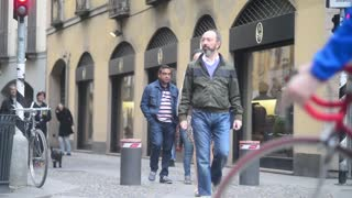 People pedestrians walking by street of center Milan Italy spring day